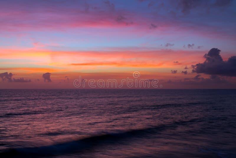 Den dramatiska rosa solnedgången fördunklar över vattenhavet arkivbild
