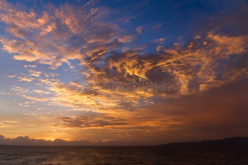 Den dramatiska solnedgången fördunklar över vattenlandskap arkivfoto
