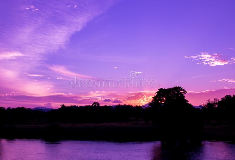 Den dramatiska solnedgången i himmel och reflekterar för signalblått för floden härlig färgrik intelligens för tid för skymning f royaltyfria foton