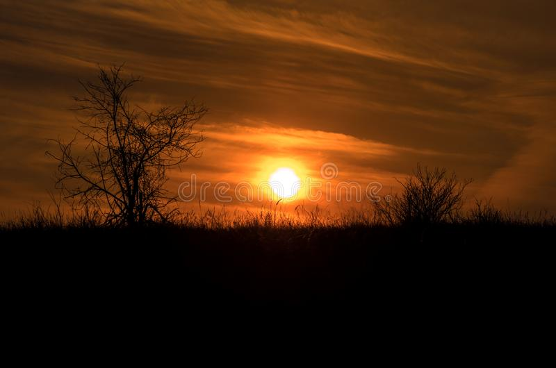 Den dramatiska solnedgången rays till och med en molnig mörk himmel ovanför berget fotografering för bildbyråer