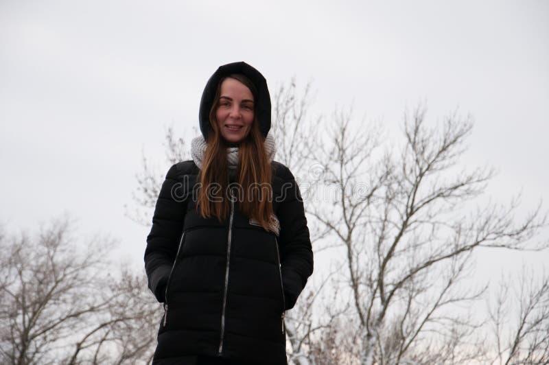 Den dramatiska ståenden av en ledsen ung kvinna i en vinter parkerar arkivbilder