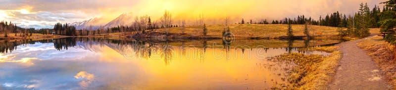 Den dramatiska vårsolnedgången färgar det blåa sjöKanada landskapet Alberta Foothills arkivbilder