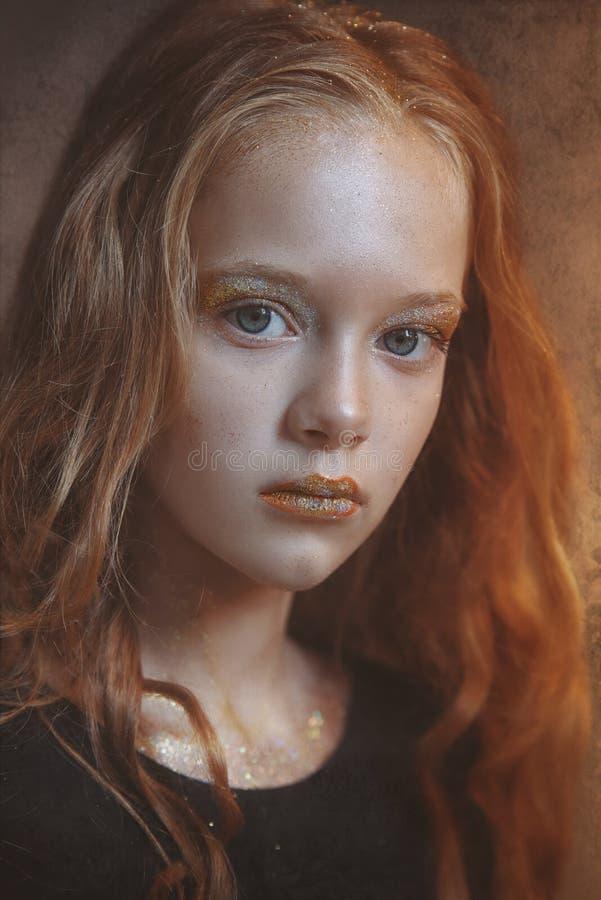 Den dramatiskt ståenden av en ung rödhårig manflicka med ljus makeup och färgrikt blänker och mousserar på hennes framsida fotografering för bildbyråer