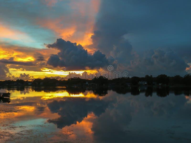 Den dramatiskt stolpe-stormen, ljus och mörkersolnedgången som reflekterar över stillhet, träd-fodrade sjön i Florida arkivbild