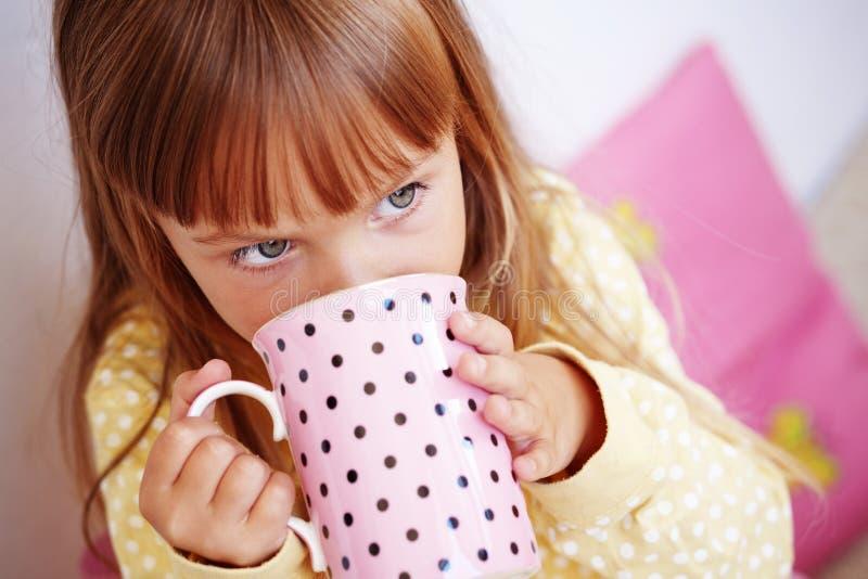 den dricka flickaungen mjölkar arkivfoton