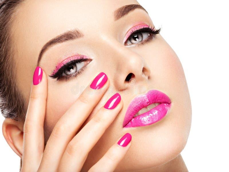 Den Eautiful kvinnaframsidan med rosa makeup av ögon och spikar arkivfoton