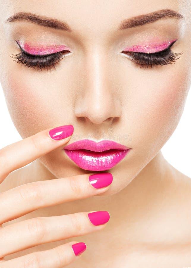 Den Eautiful kvinnaframsidan med rosa makeup av ögon och spikar royaltyfri foto
