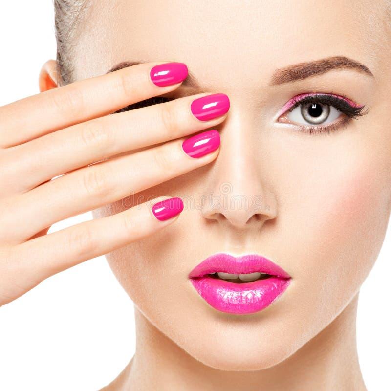 Den Eautiful kvinnaframsidan med rosa makeup av ögon och spikar royaltyfria bilder