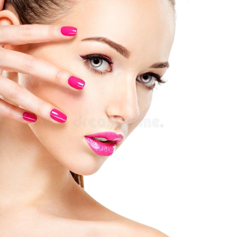 Den Eautiful kvinnaframsidan med rosa makeup av ögon och spikar arkivbild