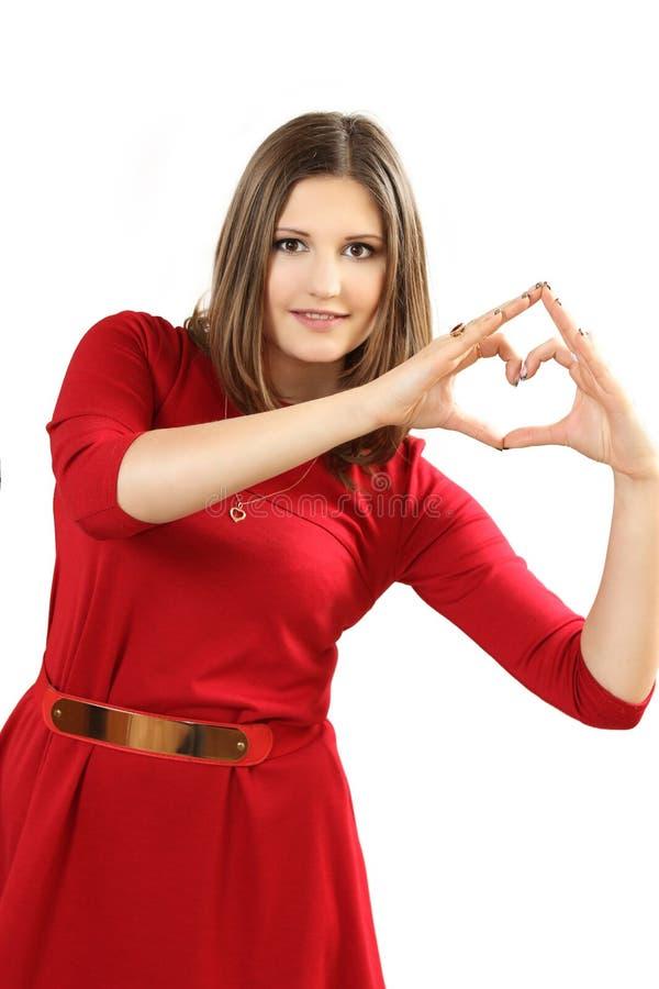 Den effektiva unga kvinnan i en röd klänning med röd hjärta Valentin royaltyfria foton