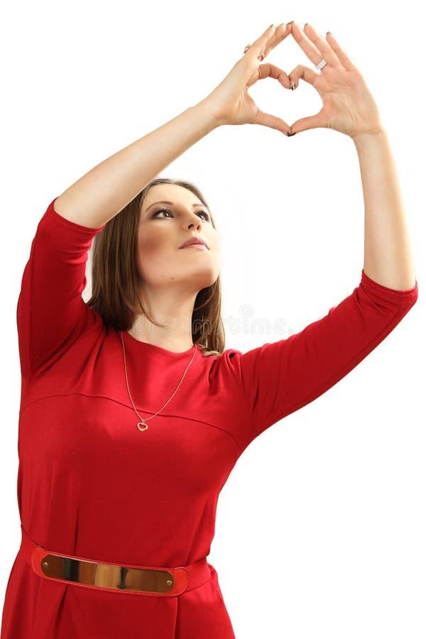 Den effektiva unga kvinnan i en röd klänning med röd hjärta Valentin royaltyfria bilder