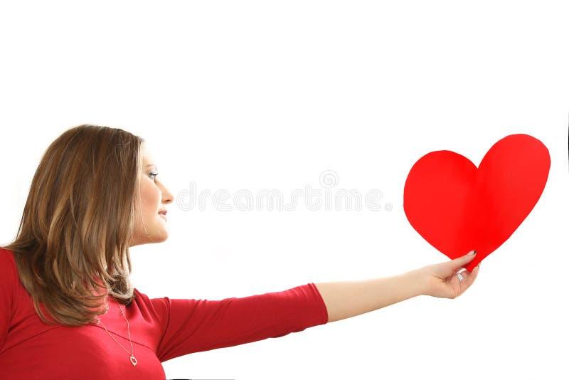 Den effektiva unga kvinnan i en röd klänning med röd hjärta Valentin arkivbilder