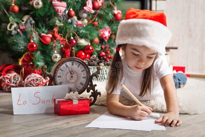 Den eftertänksamma flickan i jultomtenhatt skrivar brevet till jultomten arkivfoto