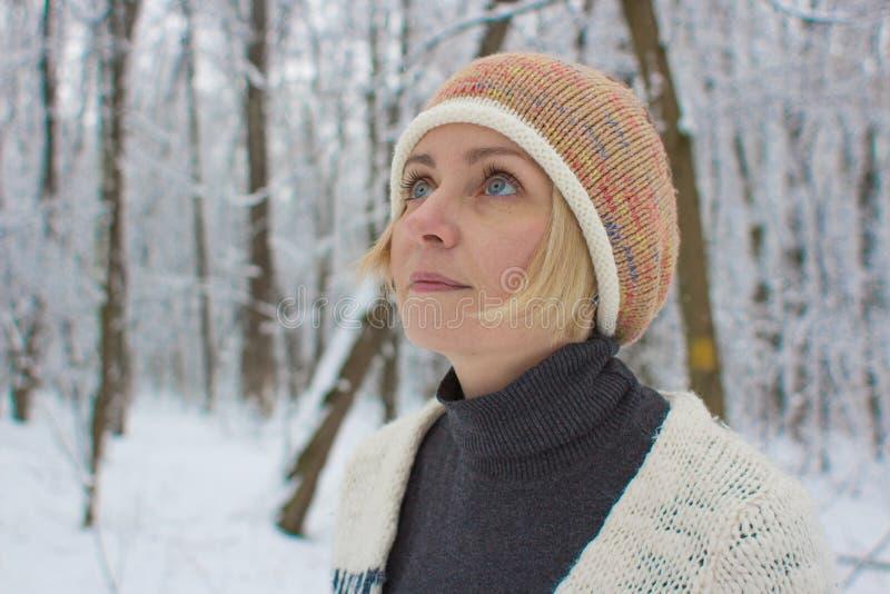 Den eftertänksamma kvinnan i vinterskogen ser himlen arkivfoto