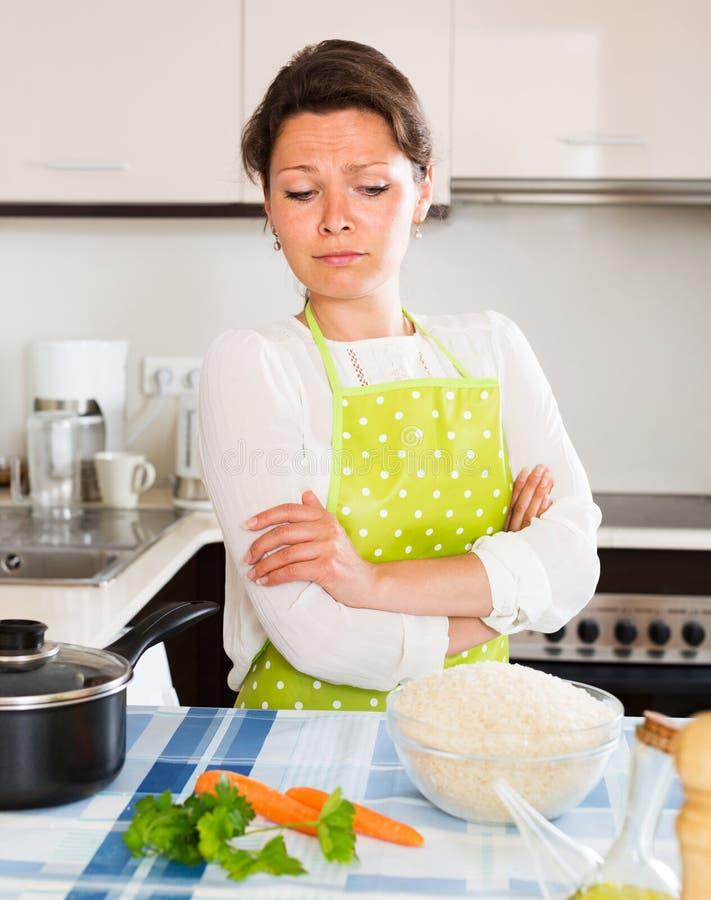 Den eftertänksamma kvinnan lagar mat ris med grönsaker royaltyfria bilder