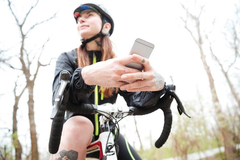 Den eftertänksamma kvinnan på cykeln som använder mobiltelefonen parkerar in royaltyfri bild
