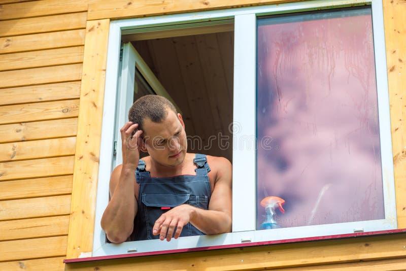 Den eftertänksamma mannen i overaller reflekterar på tvätt av fönstret royaltyfri bild