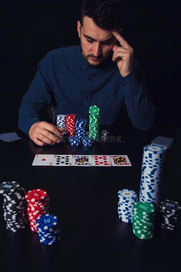 Den eftertänksamma manpokerspelaren som placeras på kasinotabellen, håller handen till pannan som tänker ser så, som spela kort o arkivfoton