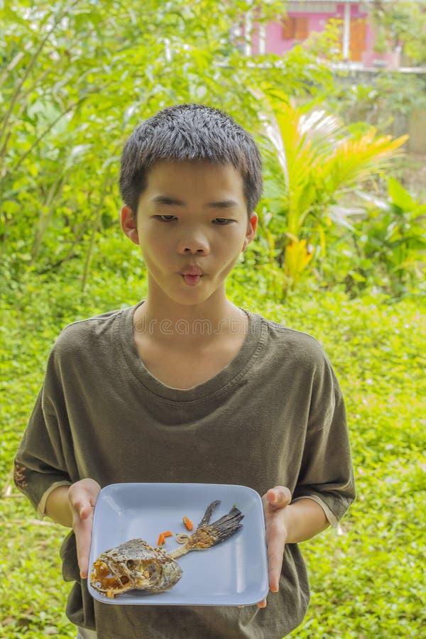 Den eftertänksamma pojken ser fiskbenet som klart ätas på plattan royaltyfri fotografi