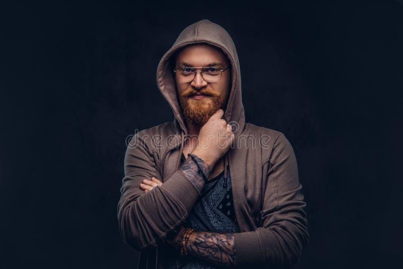 Den eftertänksamma rödhårig manhipsteren med det fulla skägget och exponeringsglas iklädd hoodie och t-skjorta poserar med handen royaltyfria bilder