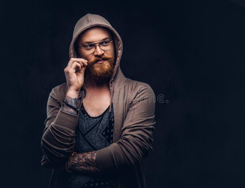 Den eftertänksamma rödhårig manhipsteren med det fulla skägget och exponeringsglas iklädd hoodie och t-skjorta poserar med handen arkivbild
