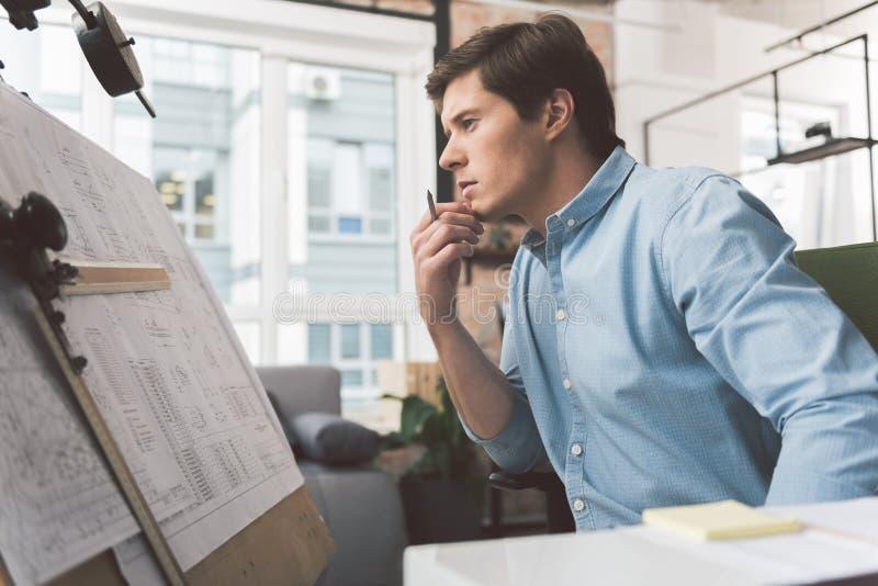 Den eftertänksamma skickliga mannen sitter i hemtrevligt kontor arkivbild