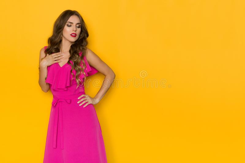 Den eftertänksamma unga kvinnan i elegant rosa klänning rymmer handen på bröstkorg och ser bort royaltyfria bilder
