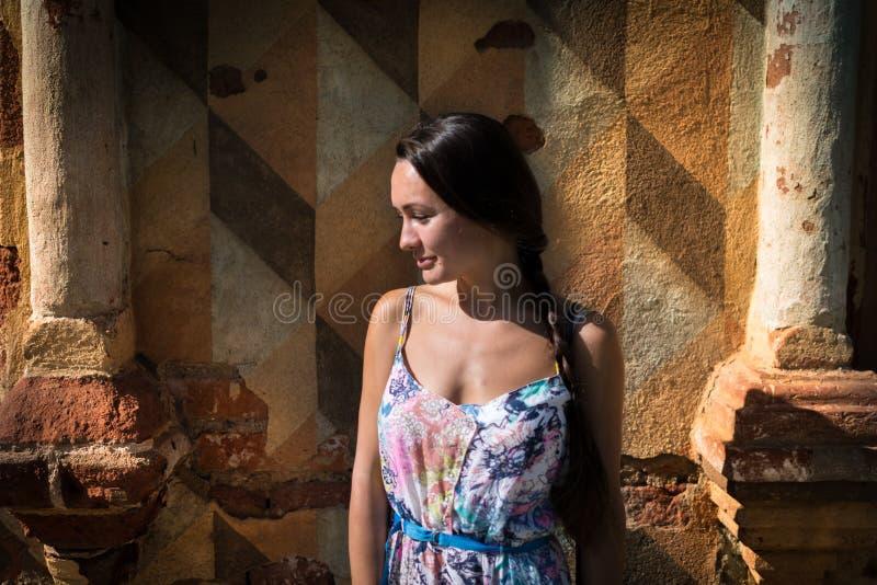 Den eftertänksamma unga kvinnan står framme av den gamla väggen fotografering för bildbyråer