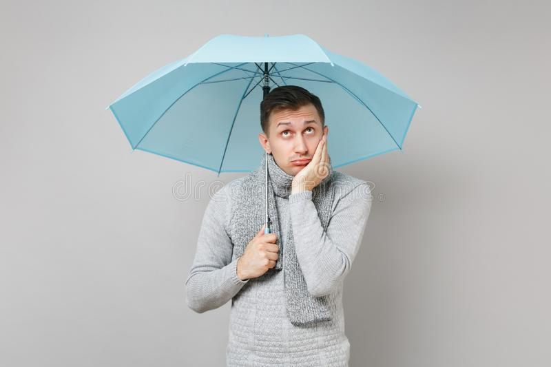 Den eftertänksamma unga mannen i den gråa tröjan, halsduk satte handen på kinden och att se upp som rymmer det blåa paraplyet iso royaltyfri foto