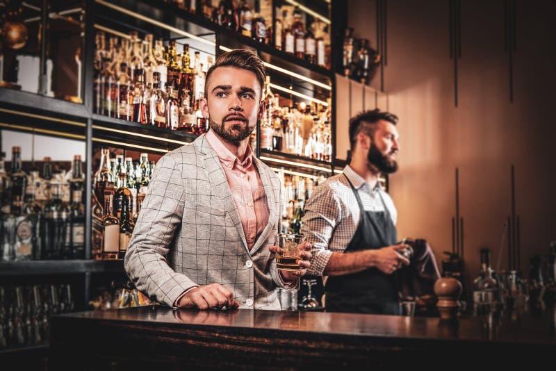 Den eleganta ansade mannen dricker alkohol på stången royaltyfria bilder
