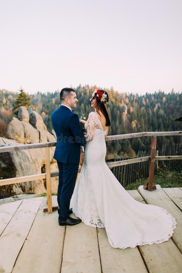 Den eleganta brudgummen i stilfulla blått passar rymma lovingly hans charmig vit klädde brudanseende på träplattformen med arkivbild