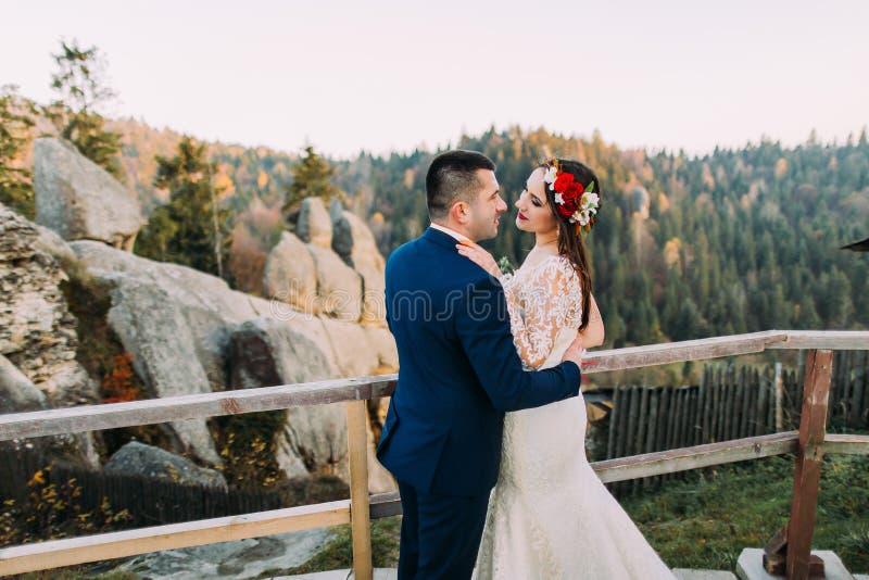 Den eleganta brudgummen i stilfulla blått passar rymma lovingly hans charmig vit klädde brudanseende på träplattformen med royaltyfri fotografi
