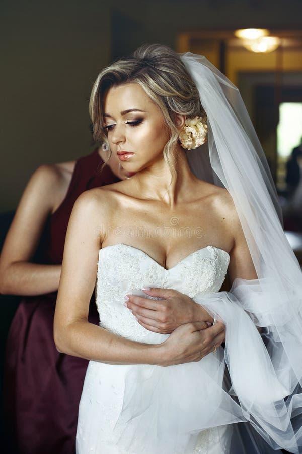 Den eleganta brudtärnan som hjälper den härliga blonda bruden, förbereder sig för oss royaltyfri bild