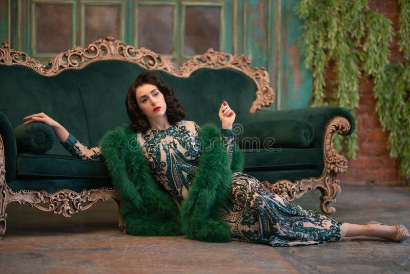 Den eleganta caucasian flickan i lyxiga långa paljetter snör åt klänningen med en grön fluffig boa i hennes händer som poserar i  arkivbild