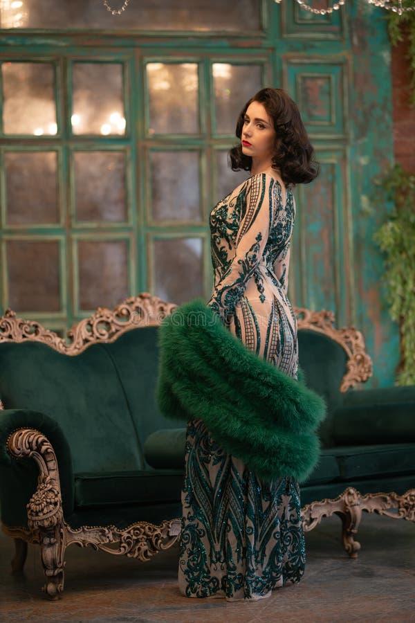 Den eleganta caucasian flickan i lyxiga långa paljetter snör åt klänningen med en grön fluffig boa i hennes händer som poserar i  arkivfoto