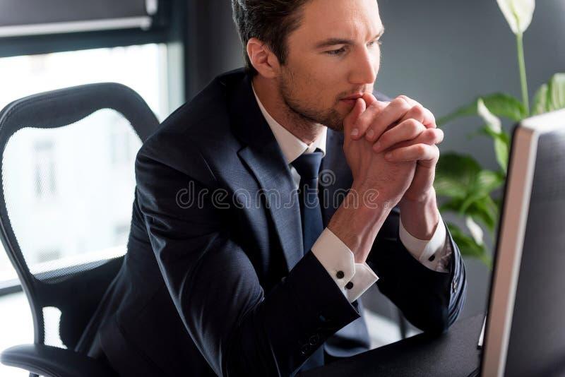 Den eleganta eftertänksamma mannen arbetar med koncentration arkivfoton