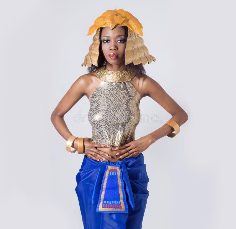 Den eleganta härliga mörkhyade kvinnan i en dräkt av den egyptiska drottningen Cleopatra i guld tonar med fängelset arkivbild