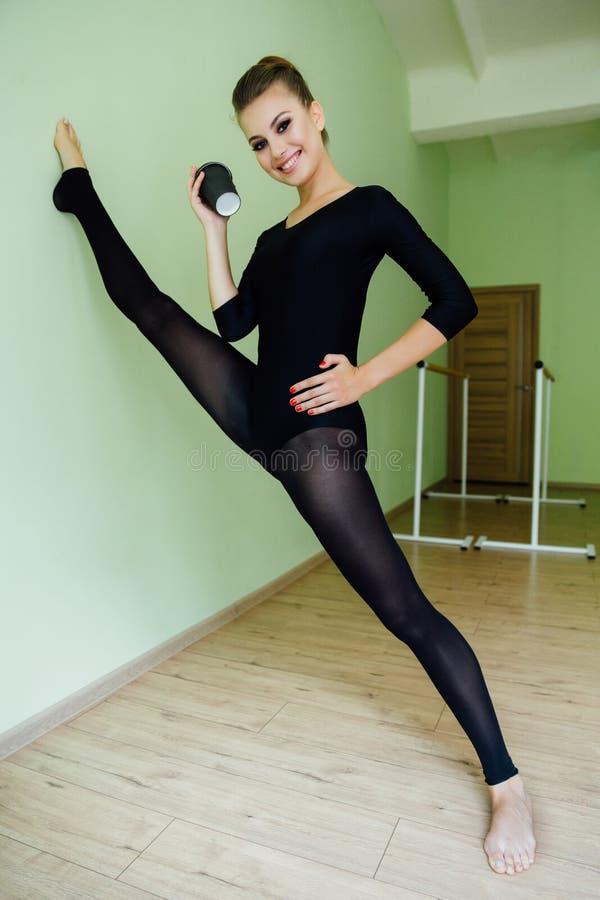 Den eleganta härliga moderna balettdansörflickan med den perfekta kroppen sitter på golvet i studiokorridoren royaltyfri bild