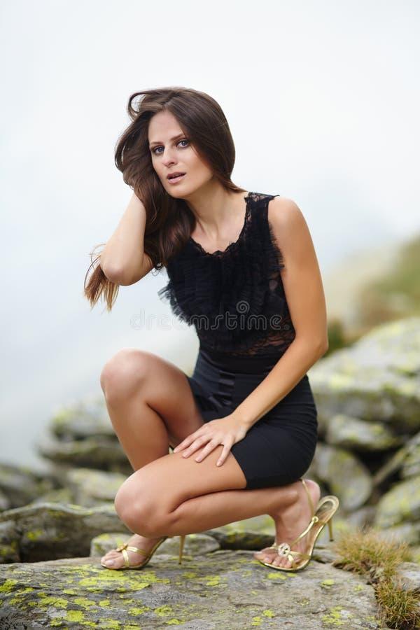 Den eleganta kvinnan i klänningsammanträde på vaggar arkivfoton