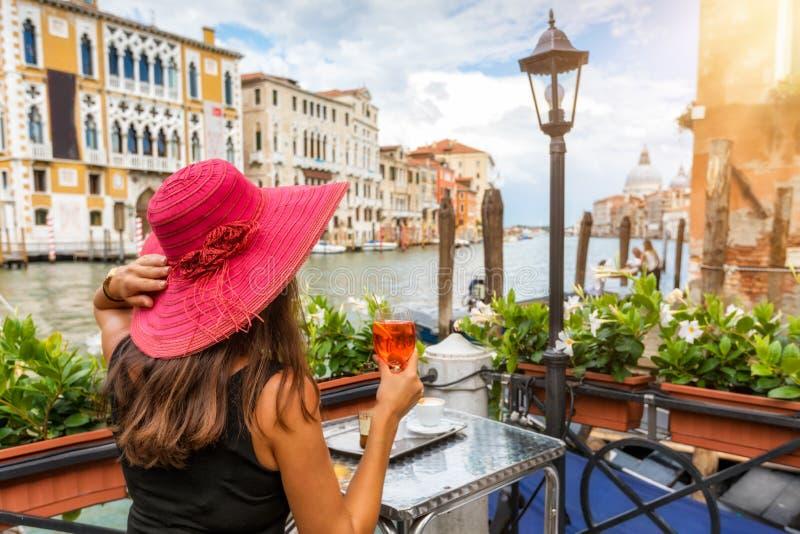Den eleganta kvinnan tycker om ett aperitifsammanträde bredvid den stora Canalen arkivbild