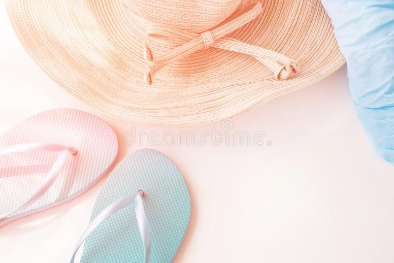 Den eleganta kvinnligStraw Hat Blue Slippers Beach sjalen på guld- rosa färger för vit bakgrund blossar sommarsemester för pastel arkivbild