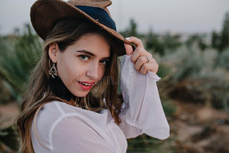 Den eleganta l?ngh?riga flickan i stilfull hatt ser tillbaka, medan g? i h?rligt exotiskt, parkerar N?rbildst?ende av n?tt fotografering för bildbyråer