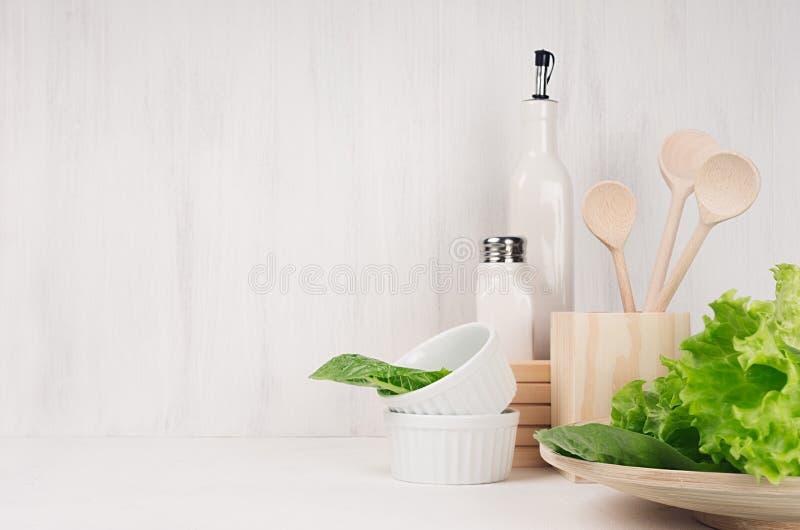 Den eleganta ljusa kökinre med träredskap, keramik och gräsplan lämnar gräsplaner på den vita wood hyllan royaltyfri foto