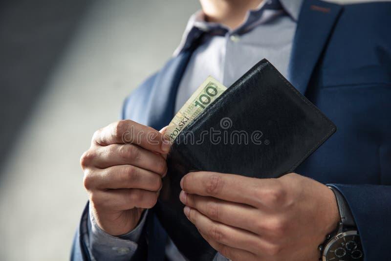 Den eleganta mannen i dräkt drar ut hans pengar från plånboken arkivfoton