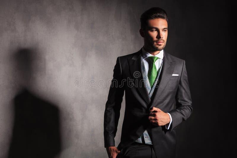 Den eleganta mannen i smokingomslag som knäppas hans lag, ser bort royaltyfria bilder