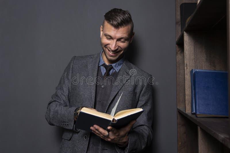 Den eleganta mannen läser boken och leenden Stilig man i dräkt med den roliga boken royaltyfri fotografi