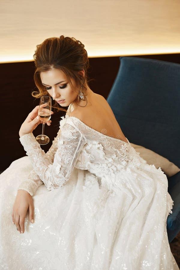 Den eleganta och härliga unga bruden, den sexiga modellflickan med exponeringsglas av champagne i hennes hand i innegrej snör åt  arkivbilder