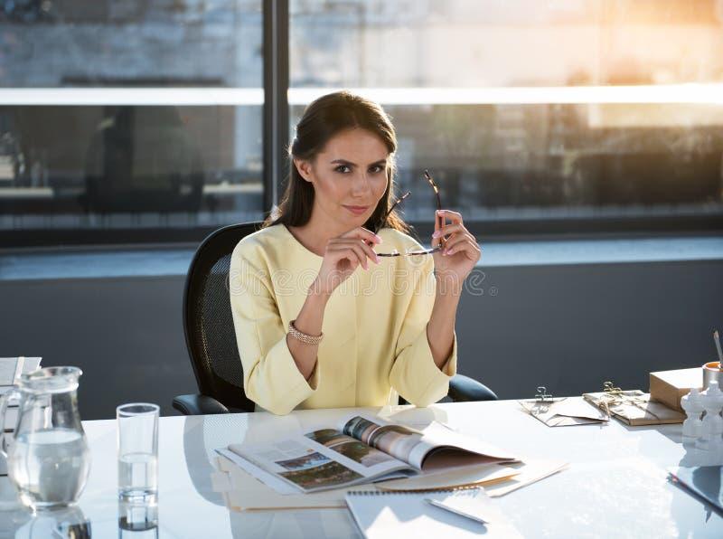 Den eleganta optimistiska flickan arbetar i regeringsställning arkivbild