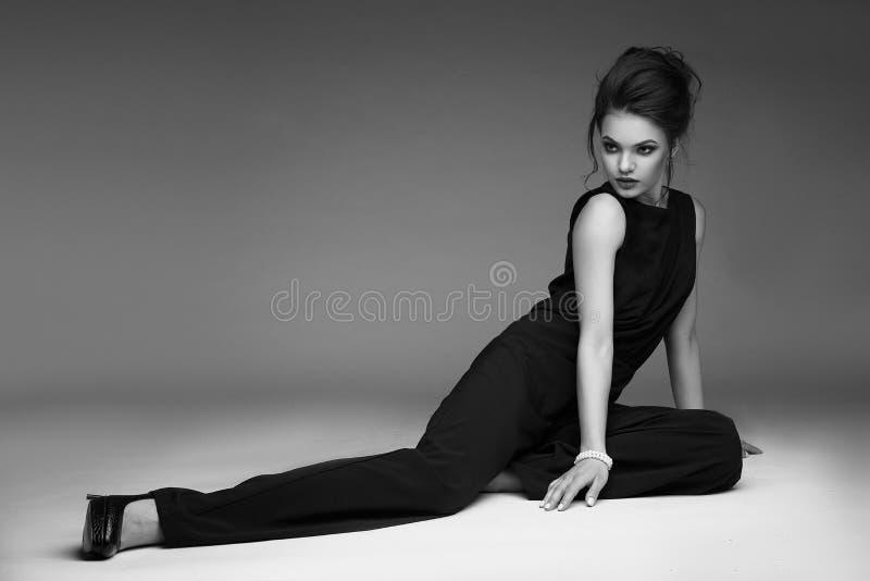 Den eleganta, säkra och smartly klädde kvinnan med frisyren, röda kanter och rökiga ögon poserar i studion arkivfoton