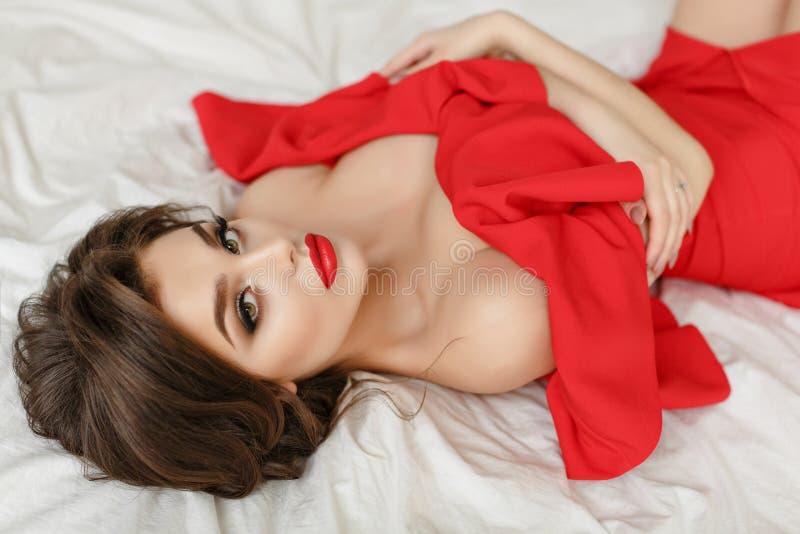 Den eleganta sexiga brunettflickan i en röd klänning ligger på en säng royaltyfria foton